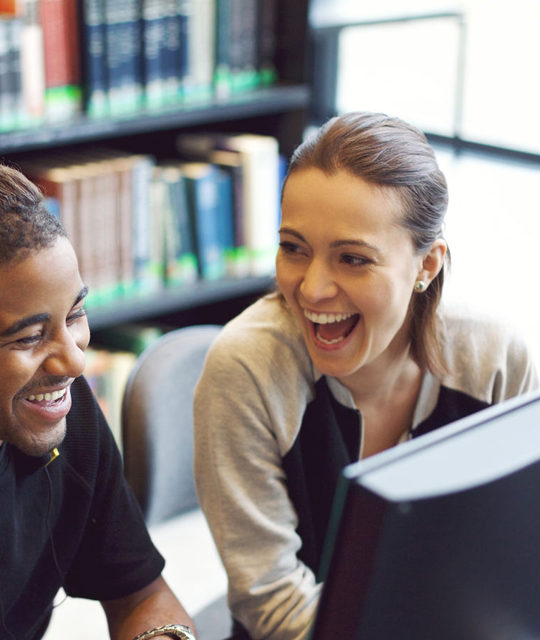 young man and woman students laughing